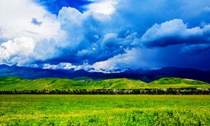 草原绿色草地和村庄摄影图片