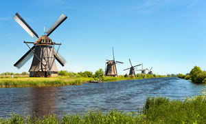 河流边上的大风车摄影图片