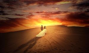 黄昏下沙漠中行走的情侣摄影图片