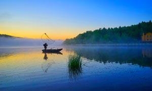 夕阳下在湖中打渔的渔民摄影图片