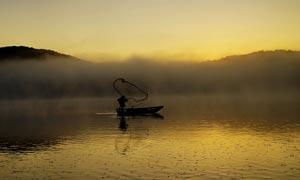 傍晚在湖中打渔的渔民摄影图片