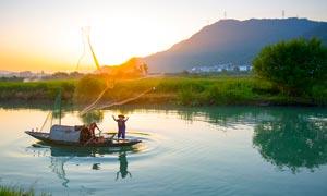夕阳下正在打渔的渔民摄影图片