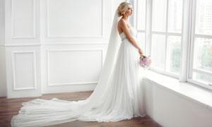 正站在窗边的洁白婚纱美女高清图片