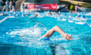 露天泳池中游泳的人物摄影高清图片