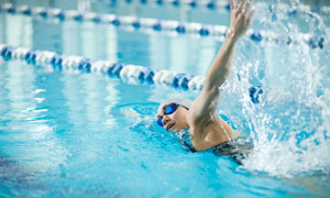 泳池中带动水花上扬的人物高清图片