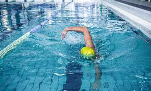 泳池中的黄色泳帽人物摄影高清图片