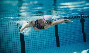 清澈泳池中的游泳人物摄影高清图片