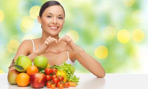 在面前放着水果的开心美女高清图片