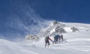 正冒着风雪登山的人群摄影高清图片