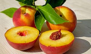 绿叶与切开的新鲜桃子摄影高清图片
