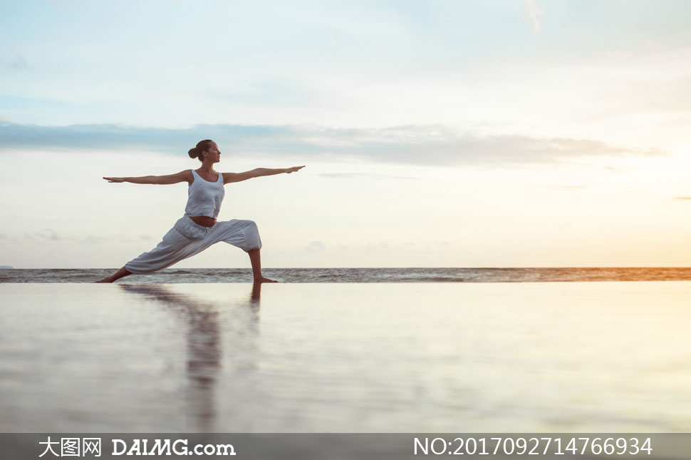 海边沙滩上的瑜伽美女摄影高清图片