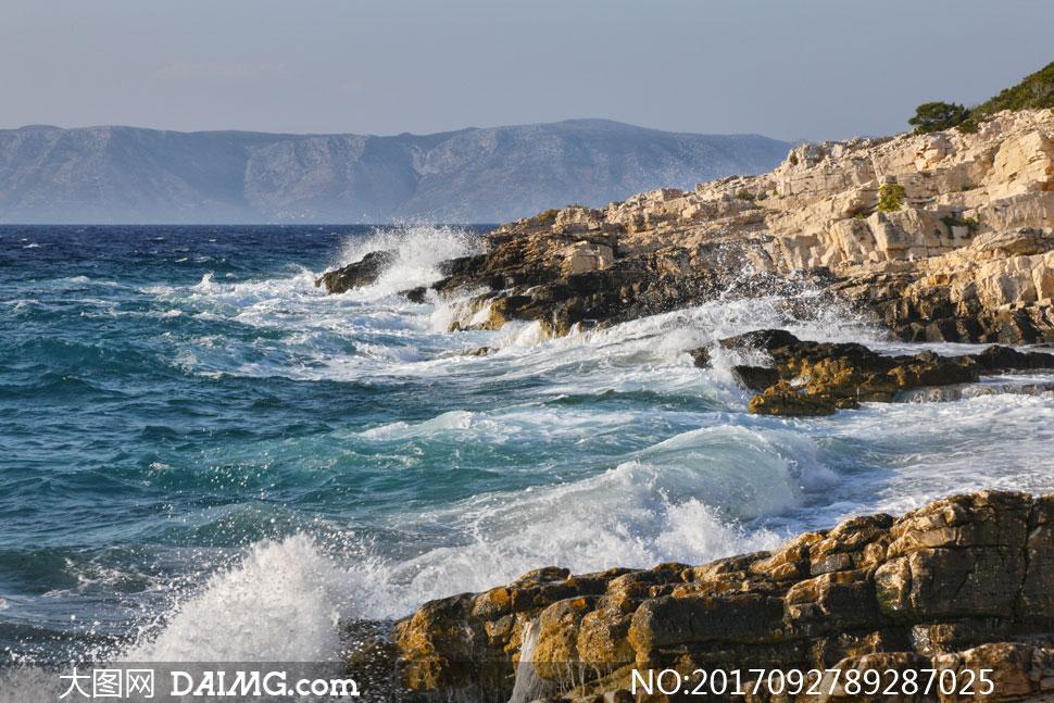 拍打着岸边礁石的海浪摄影高清图片