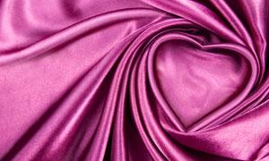 摆出心形图案的紫色布摄影高清图片