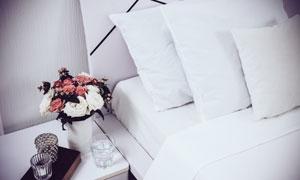 房间酒杯插花与床单枕头等高清图片