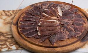 圆形砧板上的片状腊肉摄影高清图片