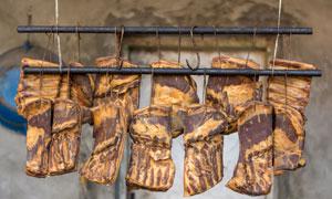 悬挂成两排晾晒的腊肉摄影高清图片