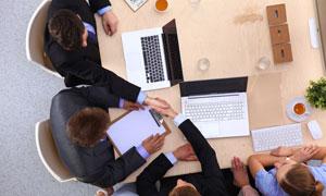 围着会议桌开会的员工摄影高清图片