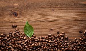 桌面上的咖啡豆与一片叶子高清图片