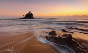 傍晚冲刷着沙滩的海水风光高清图片