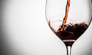 缓缓倒入酒杯的葡萄酒摄影高清图片