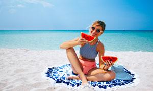 在海边沙滩上吃西瓜的美女高清图片