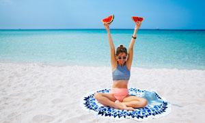 沙滩上举着两块西瓜的美女高清图片