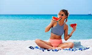 沙滩上吃着西瓜的美女摄影高清图片