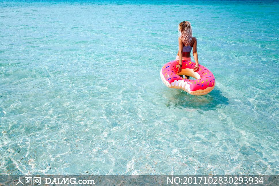 拖着可爱游泳圈下水的美女高清图片