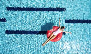 张开双臂躺游泳圈上的美女高清图片