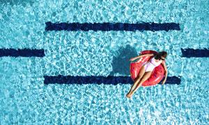 在游泳池上躺着的泳装美女高清图片