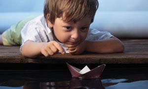 在盯着纸船看的小男孩摄影高清图片
