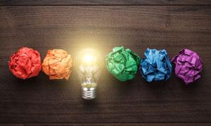 纸团与亮着的灯泡创意摄影高清图片