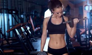 健身器械与运动装扮的美女高清图片