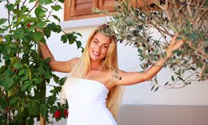 花卉植物映衬下的金发美女高清图片