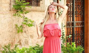 在仰望天空的粉红裙装美女高清图片