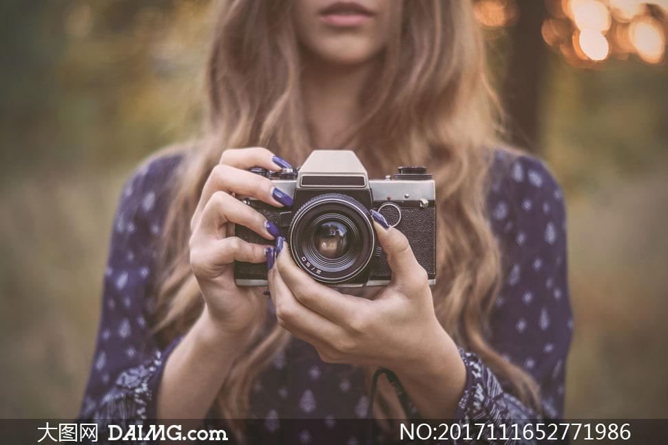 把相机拿在手中的美女摄影高清图片