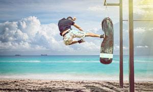 在海滩上踹沙袋的男子摄影高清图片