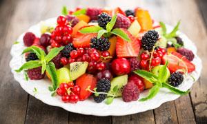 盘子里的草莓与桑葚等水果高清图片