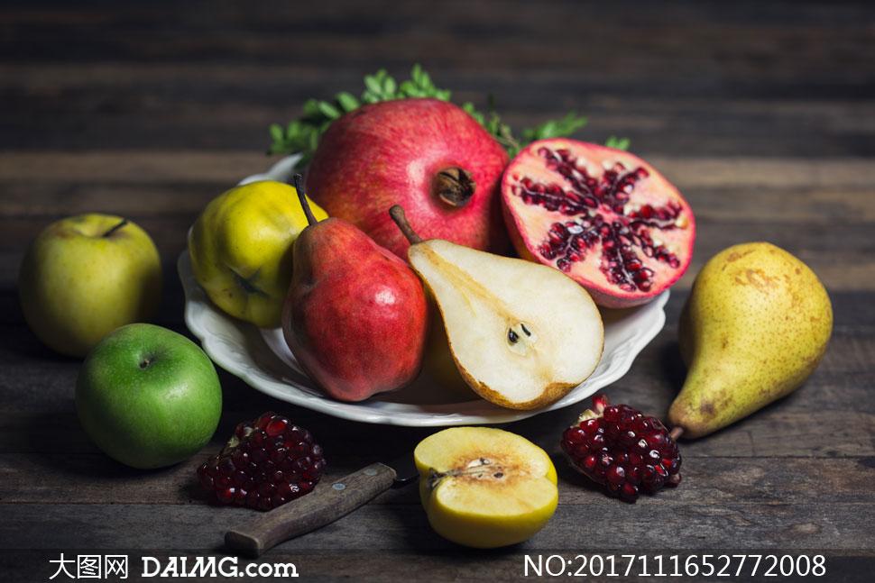 盘子里的苹果梨与石榴摄影高清图片