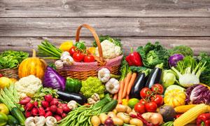 靠木板墙堆放着的蔬菜摄影高清图片