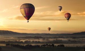 山峦树丛与飘浮着的热气球高清图片