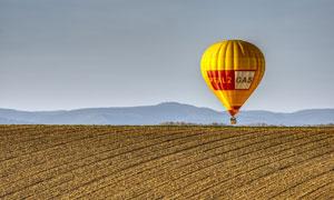 山峦与在农田上空的热气球高清图片