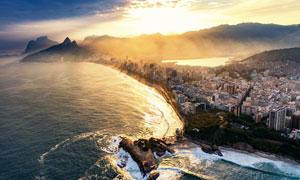 雾气霞光照耀下的海岸城市高清图片