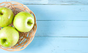 桌上果盘中的几枚苹果摄影高清图片