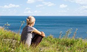 蹲着看大海风景的美女摄影高清图片