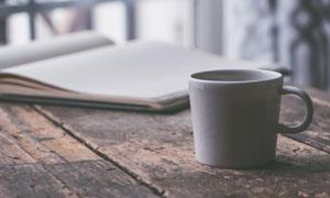 桌子上的记事本与杯子摄影高清图片