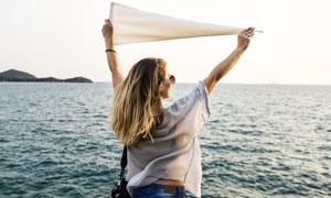 对着大海扯着布的美女摄影高清图片