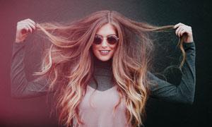 手扯着头发的开心美女摄影高清图片