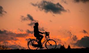 夕阳西下骑着单车的人摄影高清图片