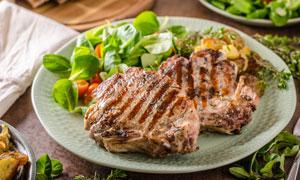 蔬菜沙拉与带骨的牛排摄影高清图片